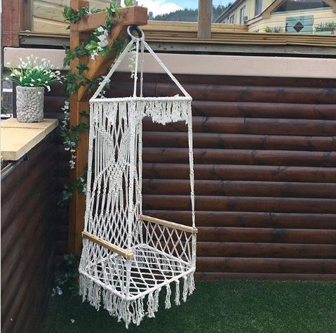 a macrame swing on a square base hanging from a beam