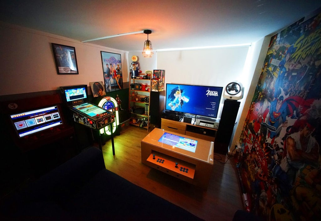 man cave room with superhero graphics on one wall, arcade machines and a jukebox