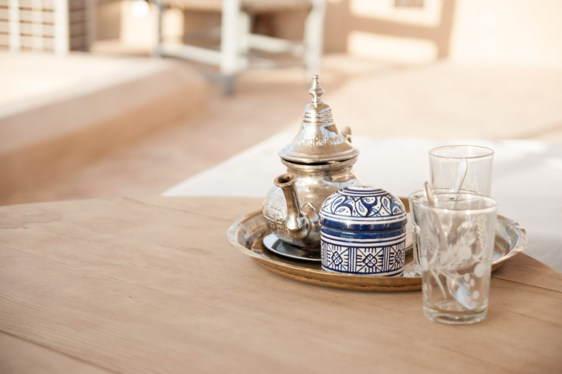 an ornate silver teapot and painted sugar bowl on a clean wooden table