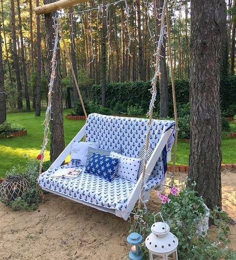 A wooden swing covered in a blanket with an anchor pattern and co-ordinating cushions