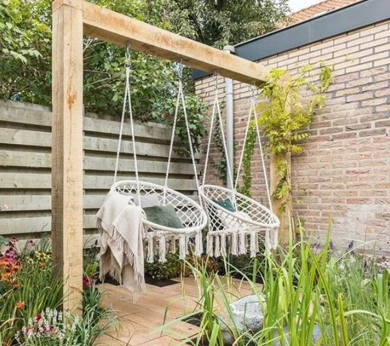 Two macrame garden swing chairs hand side by side on a wooden beam among plants