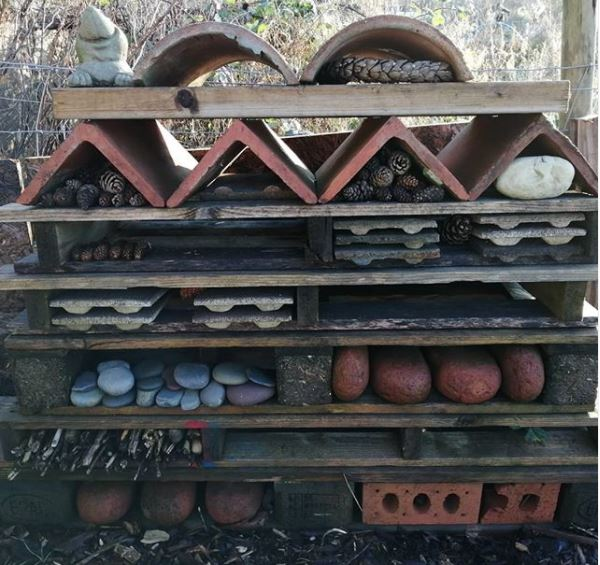 pallets, bricks, stones and clay tiles have been arranged into a large bug hotel