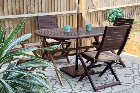 patio ideas using pale grey paving and an outdoor rug, beneath a wooden dining table and chairs