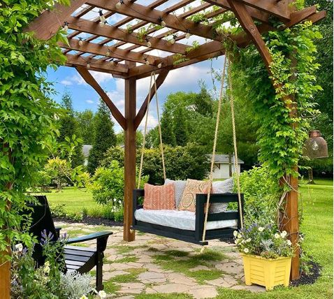 a rustic wooden bench hanging from a leaf-covered pergola
