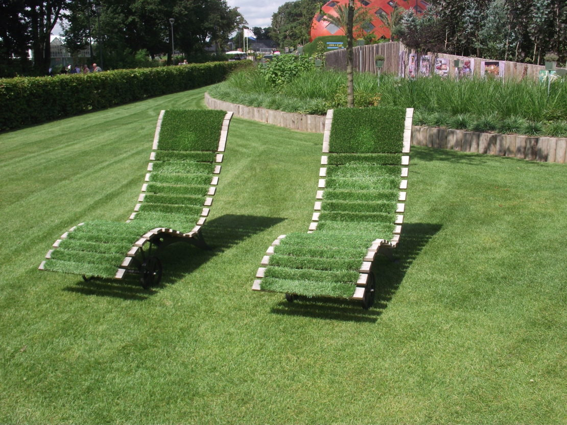 Two sun loungers in a garden, both covered with artificial grass.