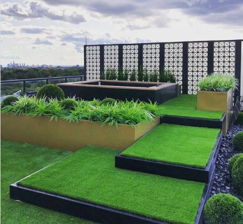 rooftop garden ideas - a stylish roof terrace with shallow steps leading up to a hot tub area, covered in artificial grass