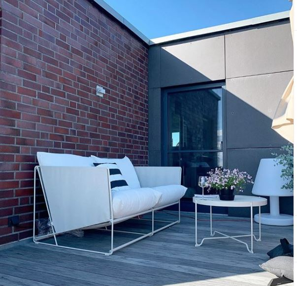 rooftop terrace ideas - wooden floor and brick walls, with slimline sofa and coffee table