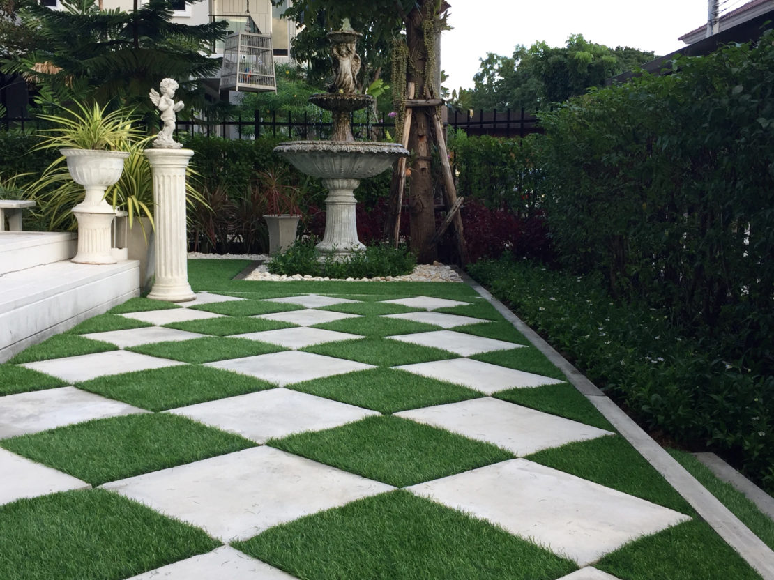 A garden with a large checkerboard pattern on the floor, made from alternating marble and astroturf tiles
