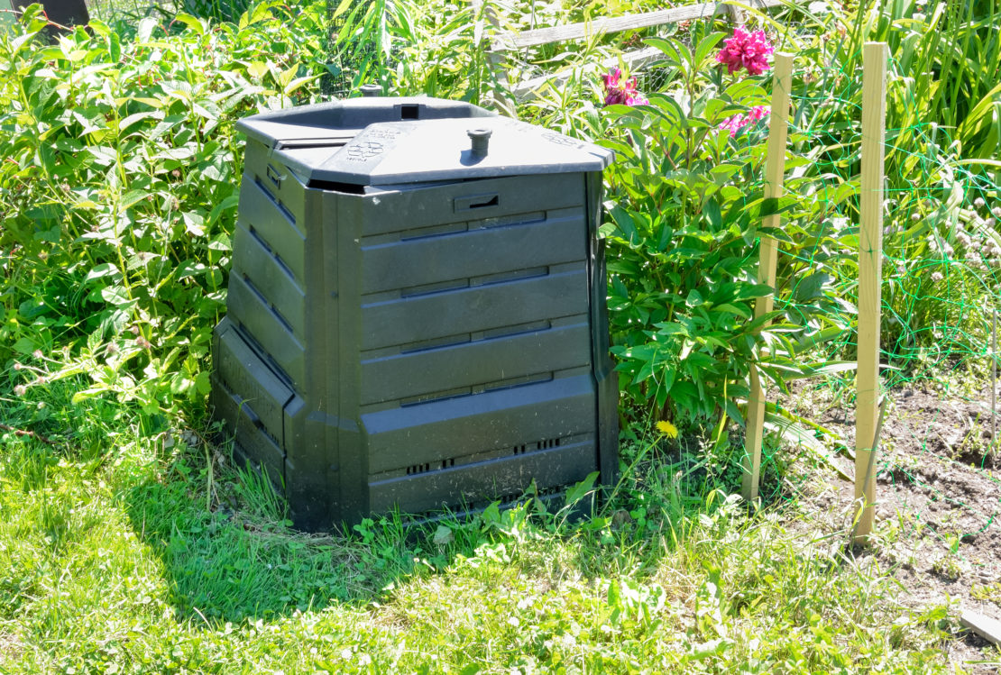 a closed compost bin with a lid, made from dark green plastic