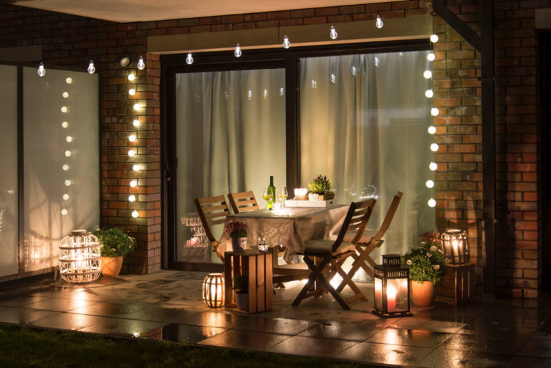 a patio dining table at night, lit by sting lights and lots of lanterns