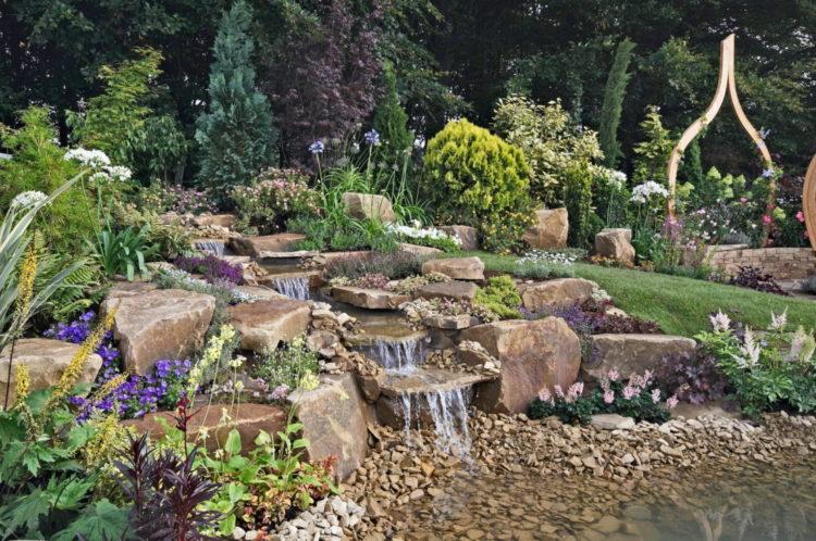 an elaborate but natural looking rock waterfall garden feature
