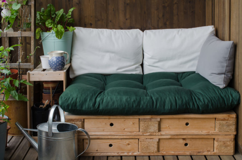 a garden seat made from two stacked pallets covered with a squashy pillow and cushioned back suppot