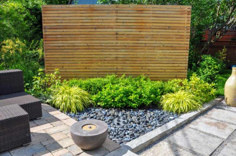 a stylish wooden screen cuts across the corner of a garden so bins can be stored behind it