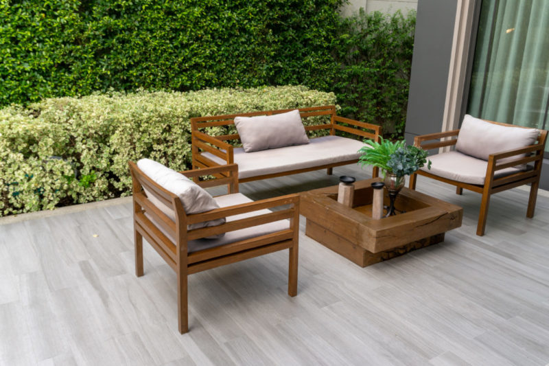 a minimalist sofa and two arm chairs made from slats of wood, with neutral coloured cushions