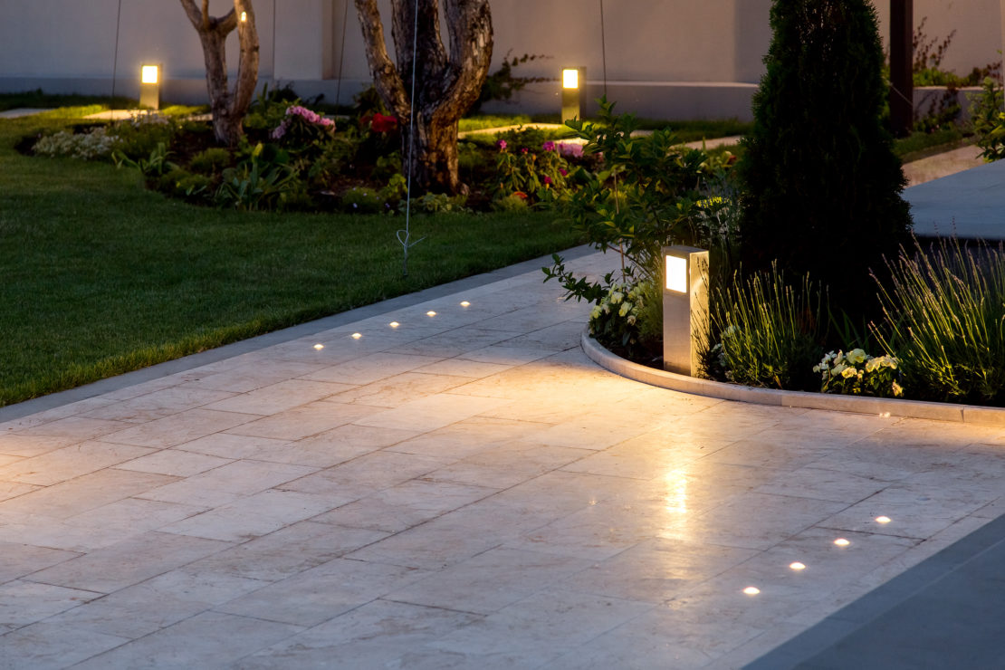 a glossy stone path with integrated spotlights and post lights shining from the flower beds