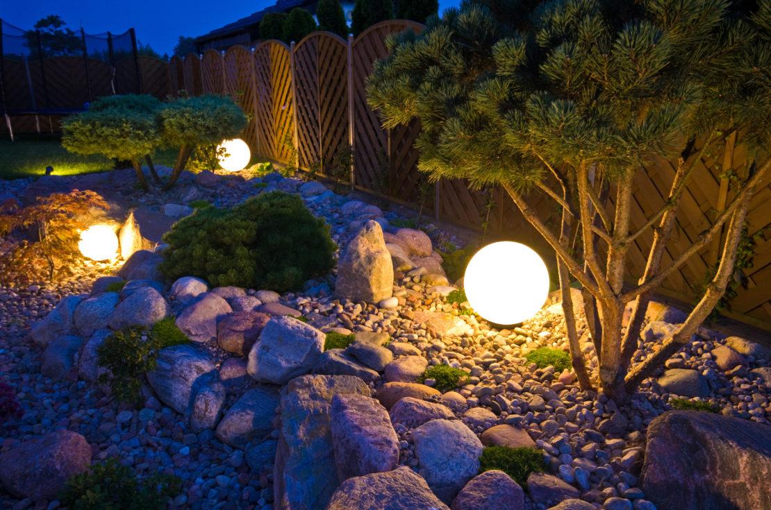 Spherical lights emitting a warm yellow glow in rocky flowerbeds