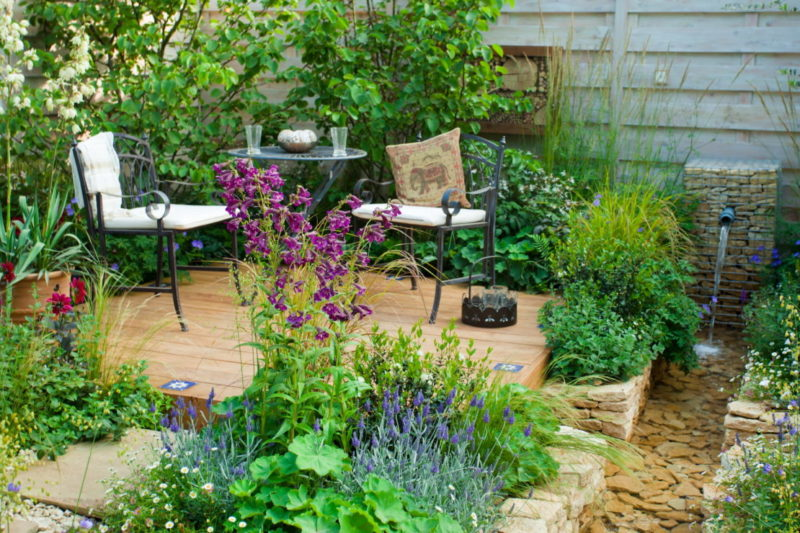 a small, busy garden with patio chairs overlooking a man-made stream