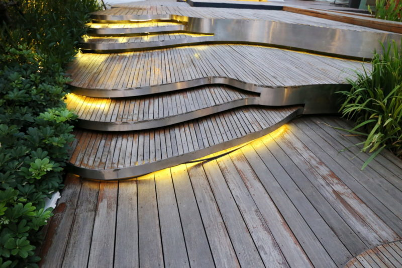 a set of wide wooden decking steps, with LED light cables hidden between the risers