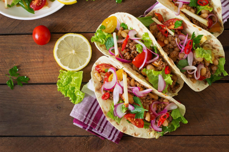 three tacos filled with peppers, onion, lettuce and fresh chillies