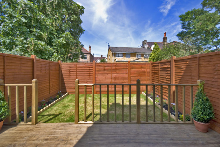 a simple rectangular garden with a deck and lawn with narrow floral borders and a sturdy looking fence