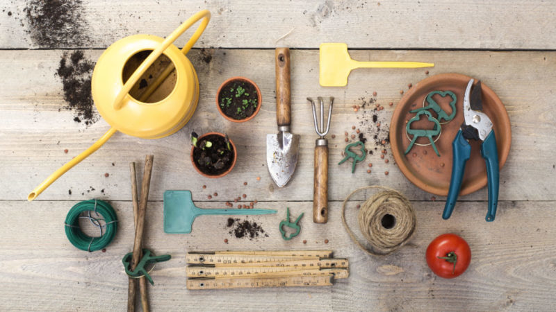 a flat-lay style image of garden tools including a watering can, trowel, fork and pots