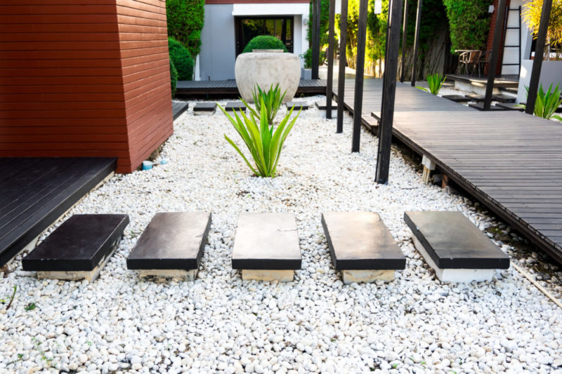 Smooth rectangular stepping stones across a bed of white pea gravel