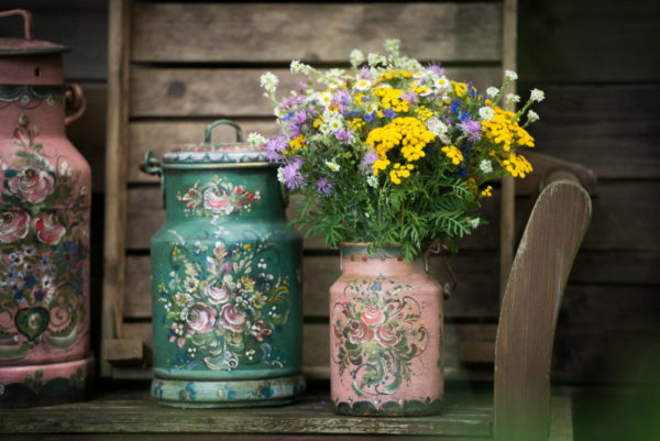 Vintage milk cans painted in pink and green with floral details