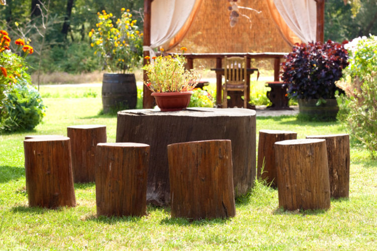 several seats made from tree stumps are sat around a larger tree stump, used as a table