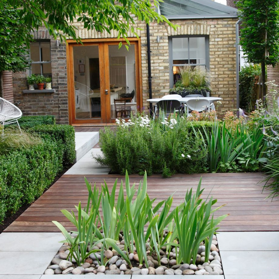 small garden ideas - a neat garden sectioned into square of plants, decking and concrete