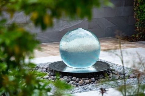 a spherical garden fountain with water gently flowing over it