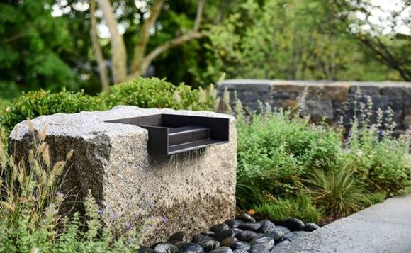 a stone block with a wide metal spout embedded, gently pouring into the gravel below