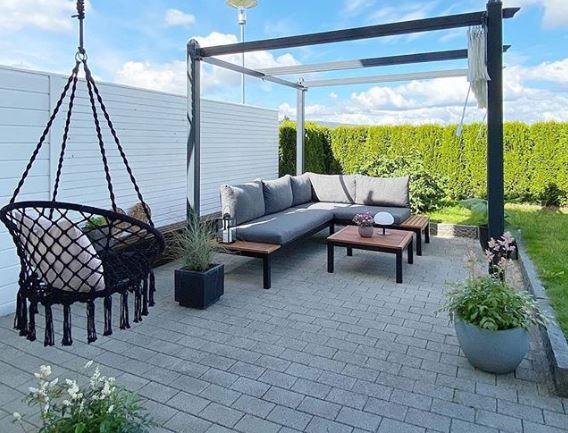 A black macrame swing seat handing next to garden sofas under a pergola
