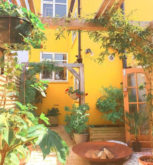 the courtyard of a bright yellow house, with a large fire bowl and lots of plants