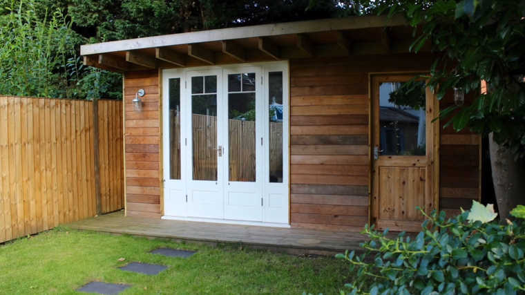 the exterior of a man cave shed with a deck at the end of a garden