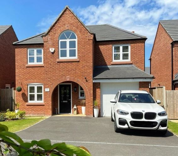 the front of a house with a crisp tarmac driveway that has space for two cars