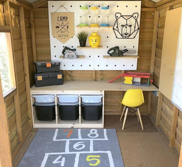 outdoor toy storage ideas using a play house with trays, baskets and a pegboard