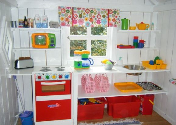 the inside of a wendy house with shelves for toy kitchenwares and storage boxes