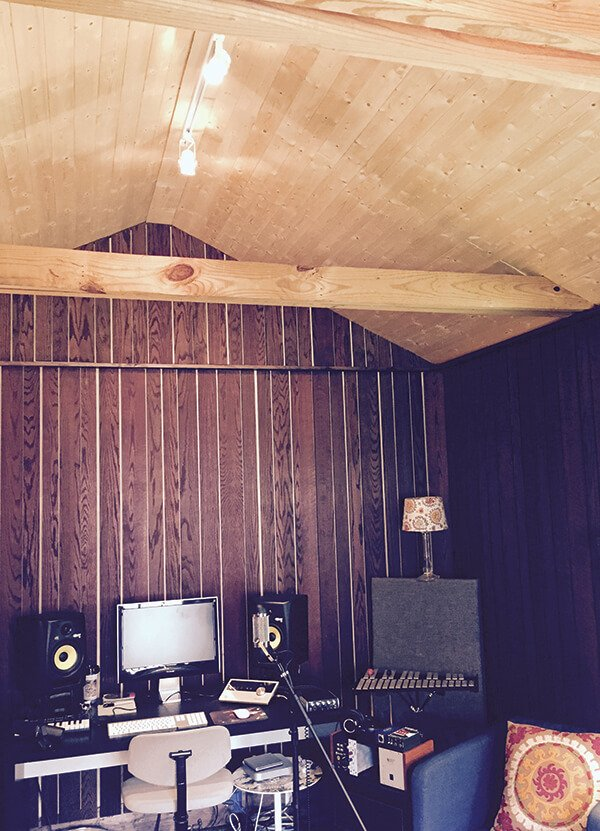 the interior of a garden shed with a pitched roof, filled with music recording equipment