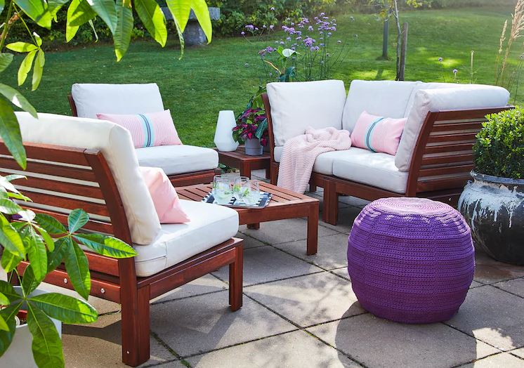 An attractive set of wooden patio furniture with cushions and foot stool
