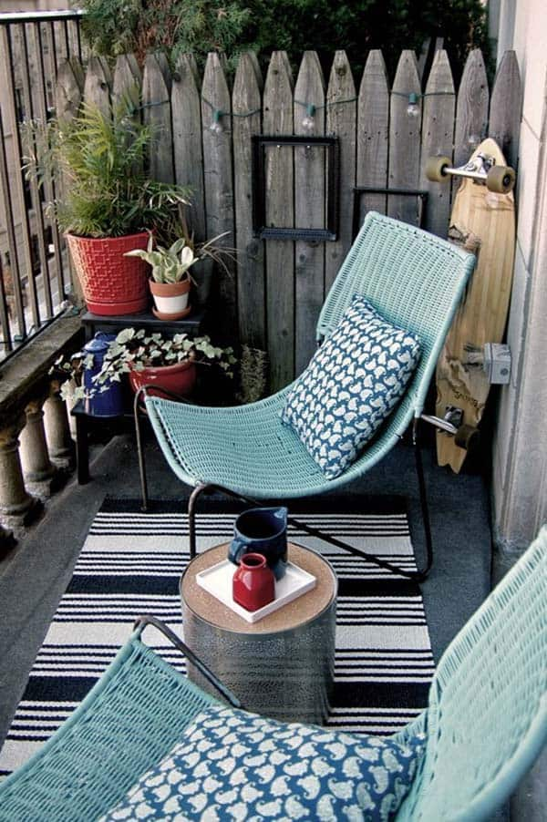 two blue wicker chairs with blue pattered cushions, contrasted with bright red plant pots