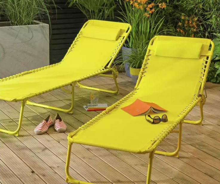 Two bright yellow portable sun loungers on a deck