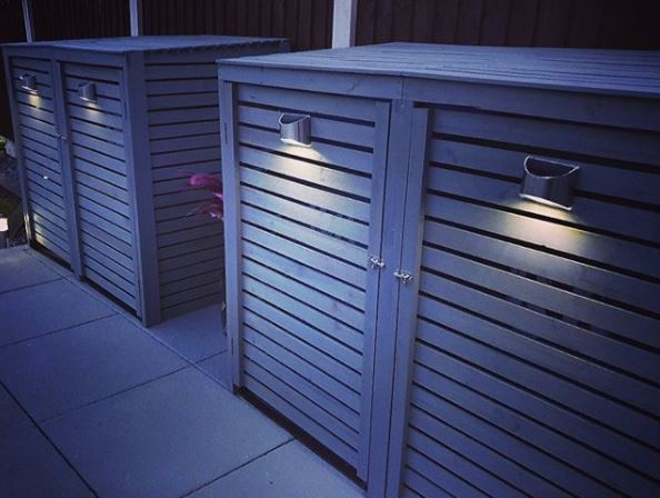 two modern bin sheds made from wood panels painted grey, with stylish metal handles that have a light fitted to them