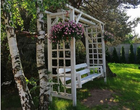 a white wooden swinging bench on a lawn, with pink flowers in hanging baskets
