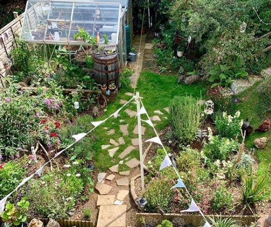 a stone patio that gradually thins out to become stepping stones in a garden with greenhouse and bunting