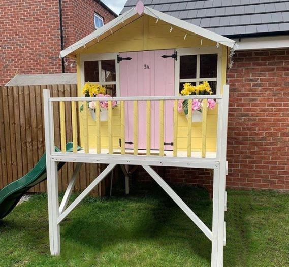 a raised playhouse with a slide coming down one side