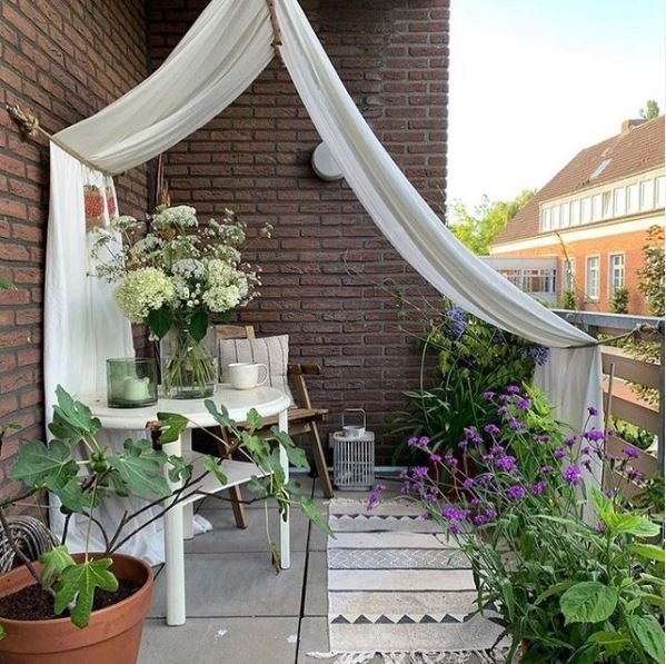 a curtain draped from the roof of a balcony, over the railings to create privacy and shade