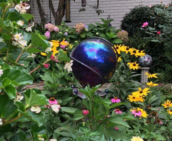 a dark blue orb makes an enchanting garden sculpture