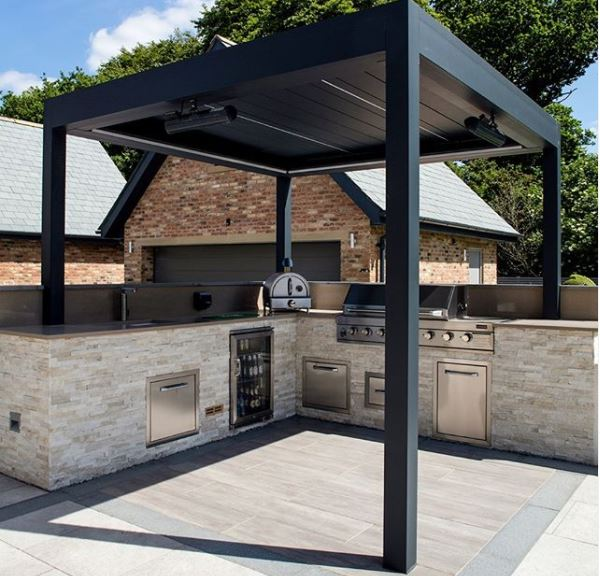 a black steel pergola with a sleek contemporary outdoor kitchen beneath