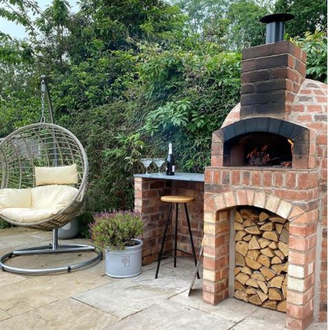 a brick pizza oven on a patio with a garden swing chair