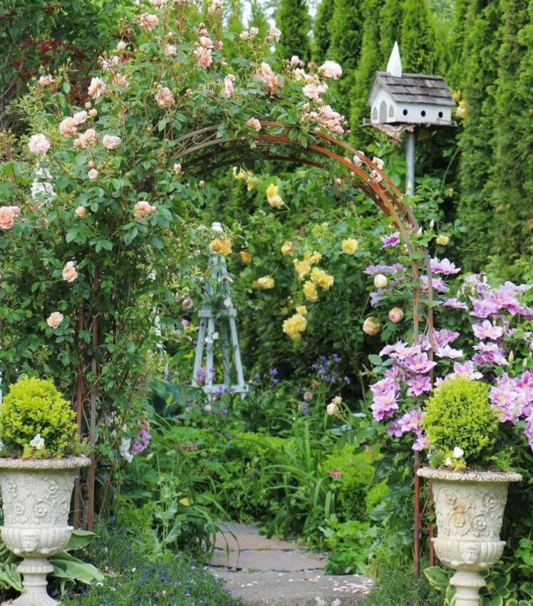 a rose-covered arbour flanked by stone planters